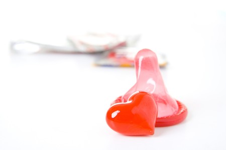 red condom: Red condom and heart isolated on white background.