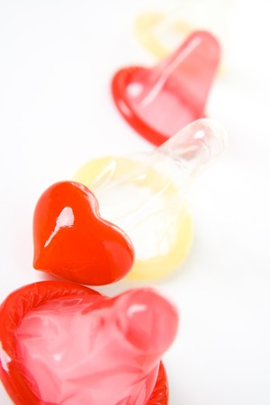 Red and yellow condoms with heart isolated on white background. photo