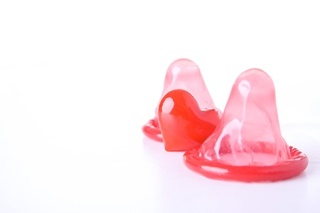 Red condoms with heart isolated on white background. photo