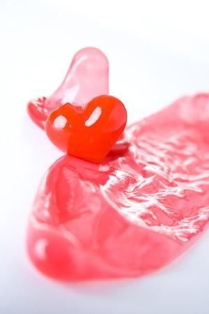 condones: Red de preservativos y coraz�n aislado sobre fondo blanco.