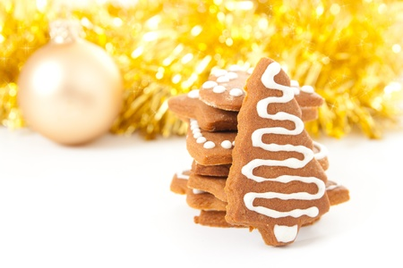 Different shaped homemade Christmas gingerbread cookies with icing and golden ribbons and bauble in background. photo