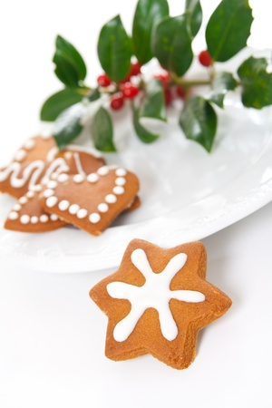 Different shaped homemade Christmas gingerbread cookies with icing and holly twig. photo
