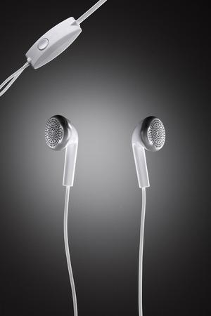 Modernly designed white headphones against circle gradient