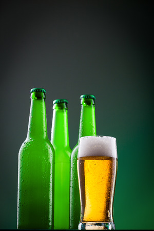 Beer bottles with glass against vivid background photo