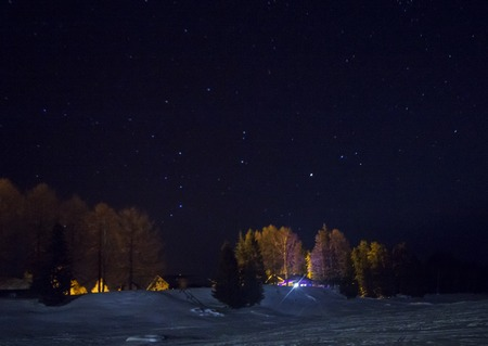 wooden house in winter at night. Winter drive way with lights far away. Imagens