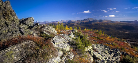 Ural autumn landscape - snow-capped peaks, mountain forests, yellow foliage, transparent cold rivers
