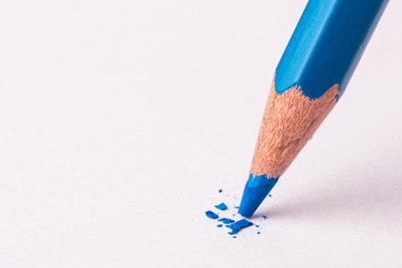 broken colored pencils on white background