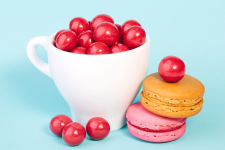 red candy chocolate ball in a cup with macaroon