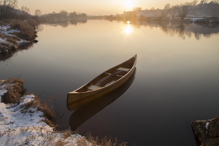 reason: new Canoe floating on the calm water in winter sunset.