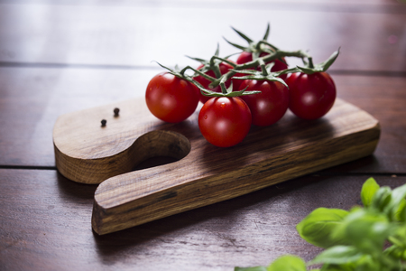 cocktail tomatoes and basil on wooden board Stock Photo