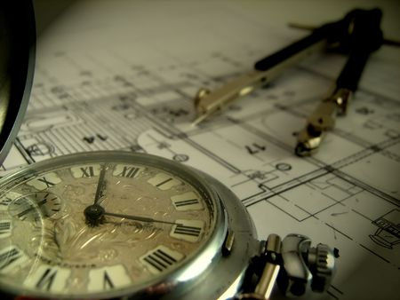 pocket watch and dividers laying on the architectural project photo
