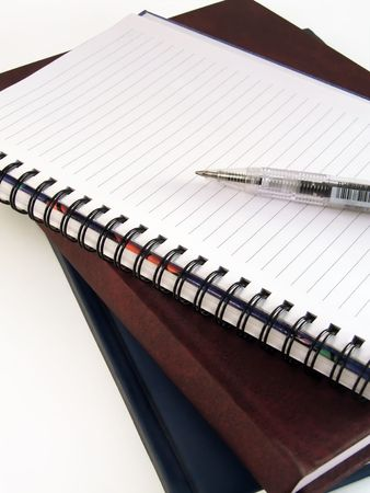 Pen laying on empty notebook and few books photo