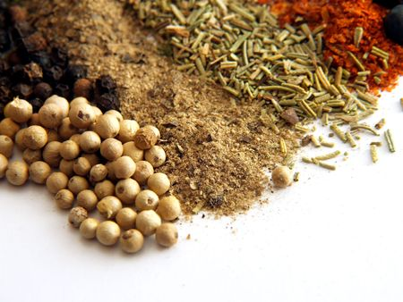 indian spice: closeup of various colorful spices over white