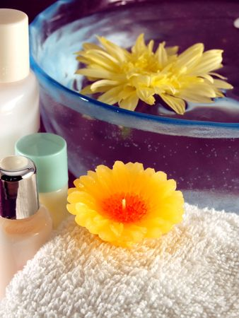 spa essentials: aromatherapy candle, towel and lotions photo