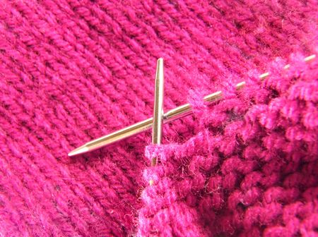 a pair of knitting needles and pink yarn photo