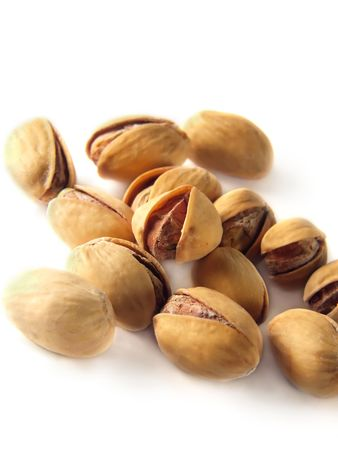 Isolated heap of pistachios on white background photo