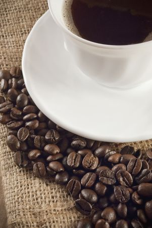 Cup of coffee with coffee beans around photo