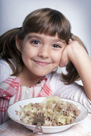 Happy little girl enjoying her lunch photo