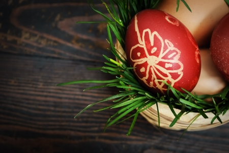 Red easter eggs in wooden basket with grass photo