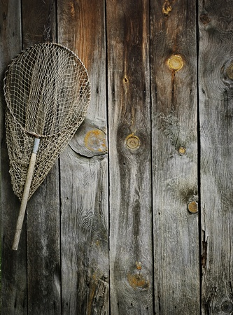 An old fishing net hanging on rustic wooden wall