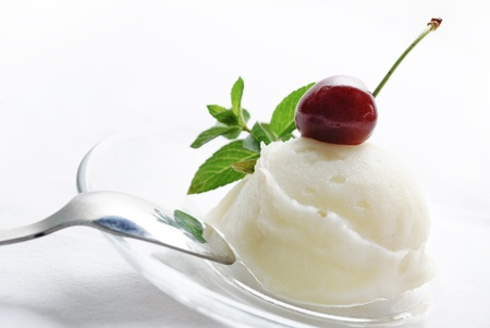 Vanilla ice cream decorated with fresh mint and cherry photo