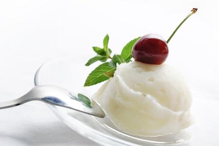 Vanille-ijs versierd met verse munt en kersen Stockfoto