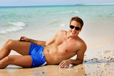 shirtless: Feliz hombre sonriente tendido en la playa Foto de archivo