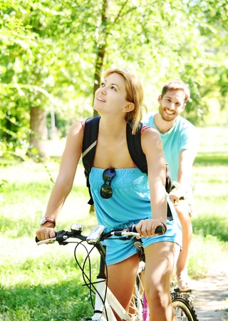 Young man and woman having a bike ride in nature photo