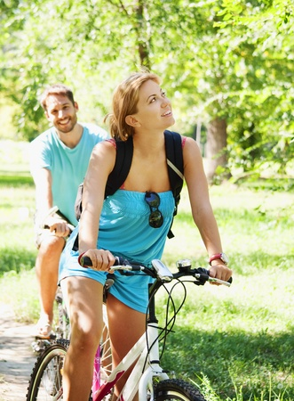 girl on bike: Young man and woman having a bike ride in nature