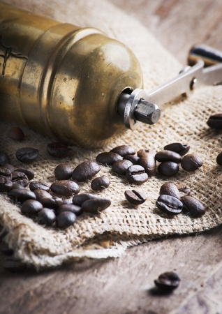 Old fashion coffee mill and coffee beans on and old sack photo