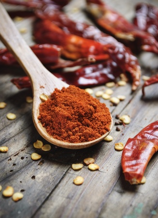 chili powder: Chilli peppers on rustick wooden plank