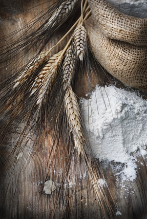 Wheat ears and flour sack on grunge wooden board photo