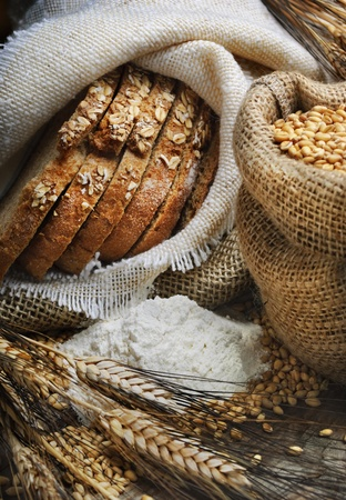 whole grains: Bread and wheat ears on vintage wooden board Stock Photo