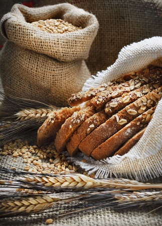 sack: Bread and wheat ears on vintage wooden board Stock Photo