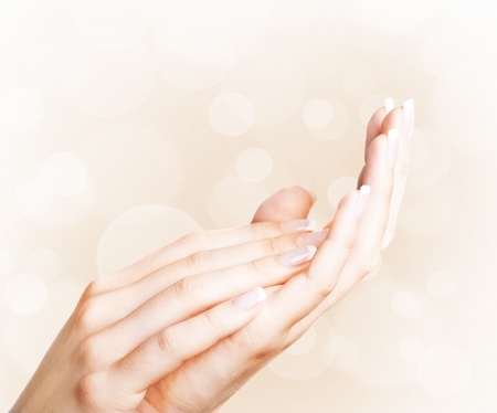 Beautiful female hands with french manicure with bokeh background photo