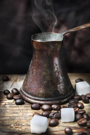 turkish coffee: Old-fashioned oriental coffee pot on grunge wooden plank Stock Photo