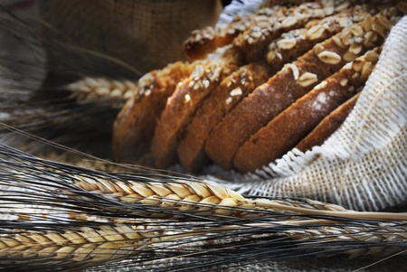 Bread and wheat ears on vintage wooden board Stockfoto