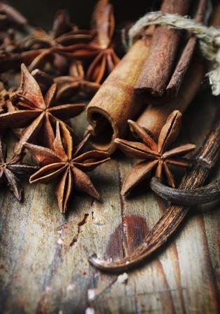 Anise seed, cinnamon and vanilla on grunge wooden plank Stockfoto