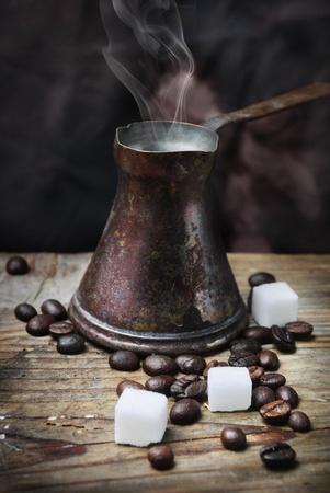 cezve: Vintage oriental coffee pot on grunge wooden plank