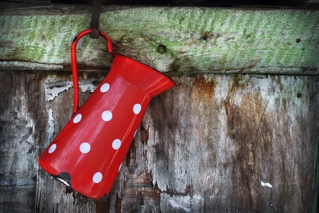 Vintage red jug hanging on rustic wooden wall Stock Photo - 12379105
