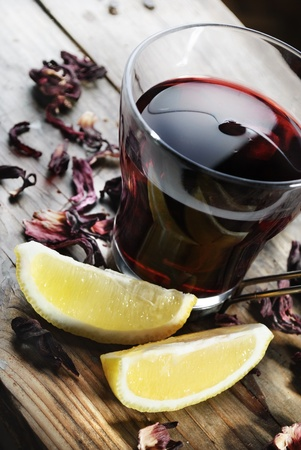 Cup of tea with dried hibiscus and lemon slices photo