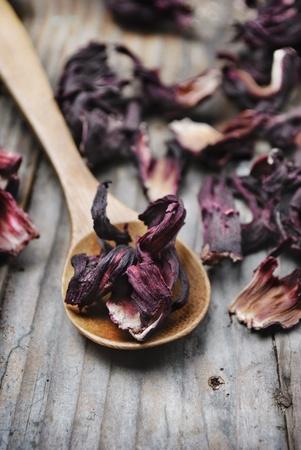 flores secas: Cuchara de t� de hibisco seco sobre fondo de madera