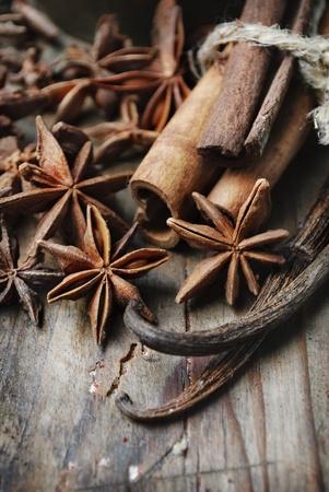 baking ingredients: Anise seed, cinnamon and vanilla on grunge wooden plank Stock Photo