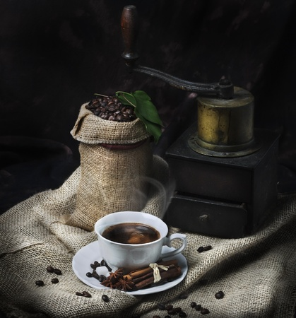 Cup of coffee and vintage coffee mill photo