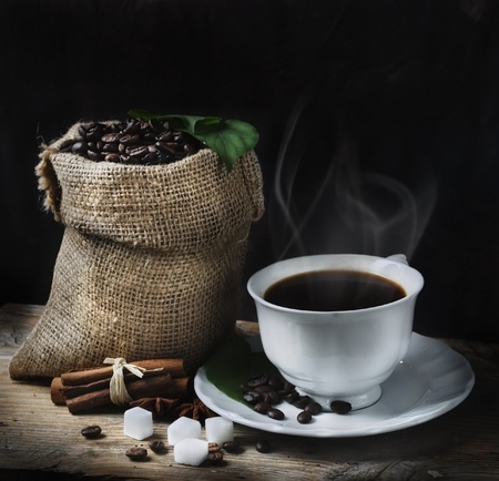 Coffee concept with coffee beans and fresh coffee leaves photo
