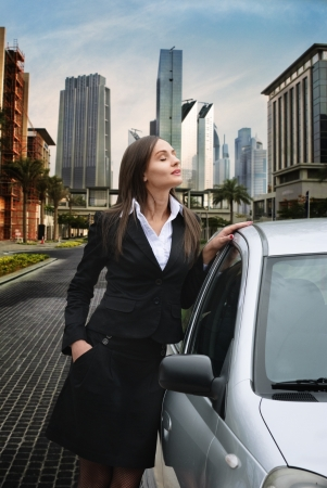 Beautiful business woman standing near her car photo