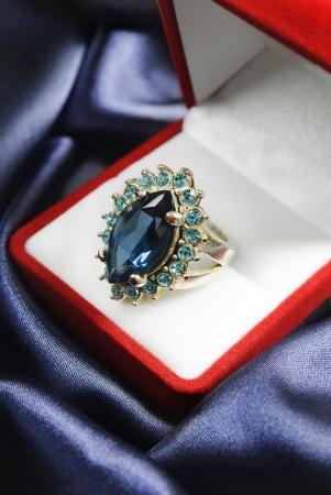 Diamond ring in jewellery box on blue silk photo