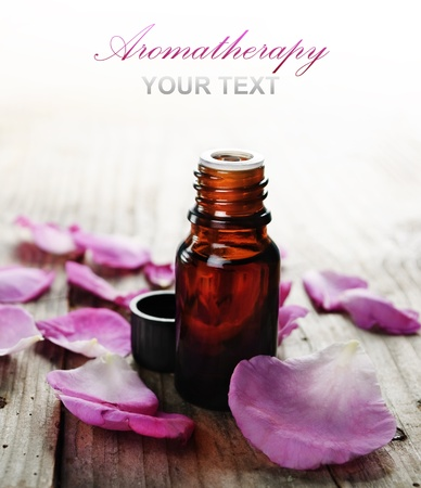 aromatherapy oils: Essential oil with rose petals on wooden background Stock Photo