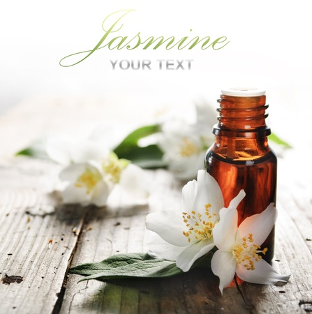 Essential oil with jasmine flower on wooden plank