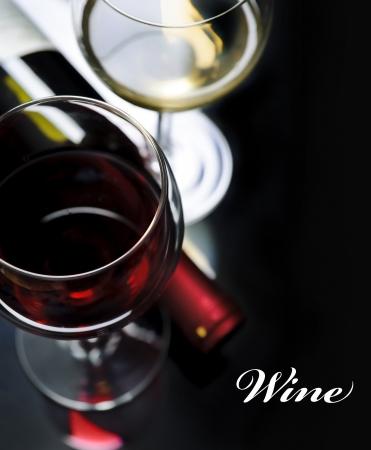 rosas amarillas: Vaso de vino tinto y blanco sobre fondo negro